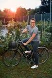 Hombre joven feliz con la bicicleta en parque Fotografía de archivo