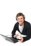 Hombre joven feliz con la computadora portátil y los auriculares Imágenes de archivo libres de regalías