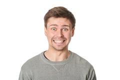 Hombre joven feliz con la expresión maníaca, en fondo gris Foto de archivo
