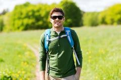 Hombre joven feliz con la mochila que camina al aire libre Imagenes de archivo