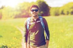 Hombre joven feliz con la mochila que camina al aire libre Imagen de archivo libre de regalías