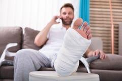 Hombre joven feliz con la pierna quebrada que habla en Smartphone fotos de archivo
