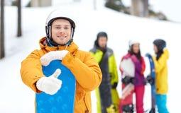 Hombre joven feliz con la snowboard que muestra los pulgares para arriba Foto de archivo libre de regalías