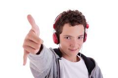 Hombre joven feliz con los auriculares rojos, y el pulgar para arriba Fotos de archivo libres de regalías