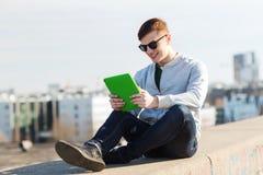 Hombre joven feliz con PC de la tableta al aire libre Fotos de archivo