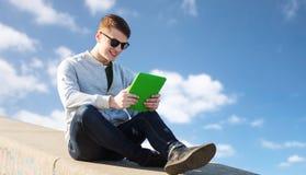 Hombre joven feliz con PC de la tableta al aire libre Foto de archivo libre de regalías