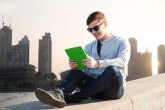 Hombre joven feliz con PC de la tableta en ciudad Foto de archivo