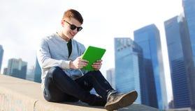 Hombre joven feliz con PC de la tableta en ciudad Imágenes de archivo libres de regalías