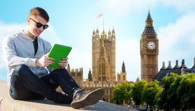Hombre joven feliz con PC de la tableta sobre la ciudad de Londres Imagen de archivo