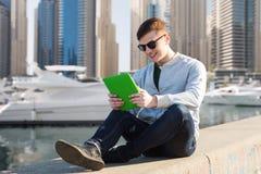 Hombre joven feliz con PC de la tableta sobre puerto de la ciudad Imagenes de archivo