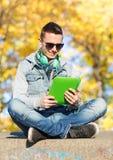 Hombre joven feliz con PC y los auriculares de la tableta Imagen de archivo