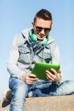 Hombre joven feliz con PC y los auriculares de la tableta Imagenes de archivo
