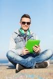 Hombre joven feliz con PC y los auriculares de la tableta Foto de archivo