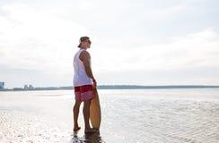 Hombre joven feliz con skimboard en la playa del verano Imagen de archivo