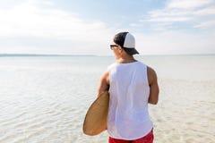 Hombre joven feliz con skimboard en la playa del verano Foto de archivo