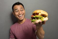 Hombre joven feliz cuando consiga una hamburguesa grande Imágenes de archivo libres de regalías