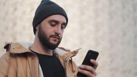 Hombre joven feliz de la barba usando smartphone en la calle cerca del centro comercial Él está llevando una chaqueta del otoño y almacen de metraje de vídeo