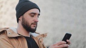 Hombre joven feliz de la barba usando smartphone en la calle cerca del centro comercial Él está llevando una chaqueta del otoño y metrajes