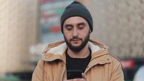 Hombre joven feliz de la barba usando smartphone que camina en la calle cerca de centro comercial Él está llevando una chaqueta d almacen de metraje de vídeo