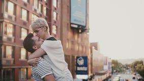 Hombre joven feliz de la cámara lenta que encuentra a su novia, deteniéndola en brazos y haciendo girar en el puente asombroso de almacen de video