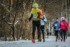 Hombre joven feliz del atleta que corre en el grupo delantero de atletas en bosque del invierno fotos de archivo
