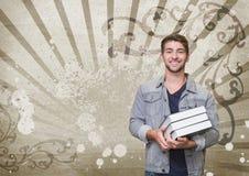 Hombre joven feliz del estudiante que sostiene los libros contra fondo salpicado marrón y blanco Foto de archivo