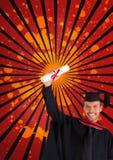 Hombre joven feliz del estudiante que sostiene un diploma contra el fondo salpicado del rojo, negro y anaranjado Fotos de archivo libres de regalías