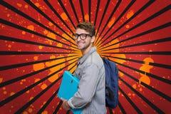 Hombre joven feliz del estudiante que sostiene una carpeta contra el fondo salpicado del rojo, negro y anaranjado Fotos de archivo libres de regalías