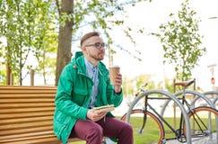 Hombre joven feliz del inconformista con café y el bocadillo Imagenes de archivo