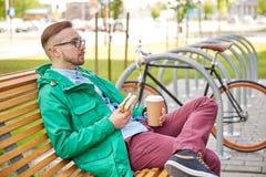 Hombre joven feliz del inconformista con café y el bocadillo Fotos de archivo libres de regalías