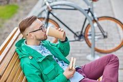 Hombre joven feliz del inconformista con café y el bocadillo Foto de archivo
