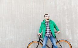 Hombre joven feliz del inconformista con la bici fija del engranaje Imágenes de archivo libres de regalías