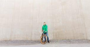 Hombre joven feliz del inconformista con la bici fija del engranaje Foto de archivo