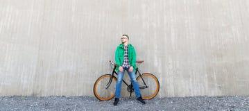 Hombre joven feliz del inconformista con la bici fija del engranaje Fotos de archivo