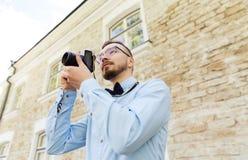 Hombre joven feliz del inconformista con la cámara de la película en ciudad Imagenes de archivo