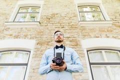 Hombre joven feliz del inconformista con la cámara de la película en ciudad Imágenes de archivo libres de regalías