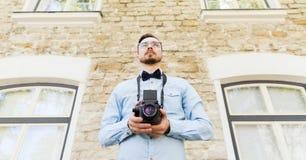 Hombre joven feliz del inconformista con la cámara de la película en ciudad Fotografía de archivo