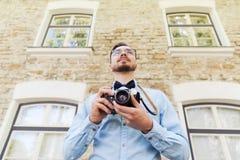 Hombre joven feliz del inconformista con la cámara de la película en ciudad Imagen de archivo libre de regalías