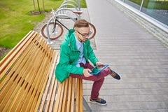 Hombre joven feliz del inconformista con PC y la bici de la tableta Imagen de archivo libre de regalías