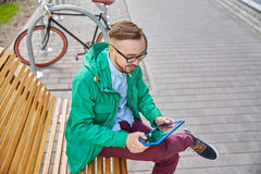 Hombre joven feliz del inconformista con PC y la bici de la tableta Imagenes de archivo