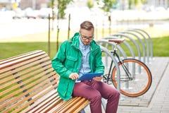 Hombre joven feliz del inconformista con PC y la bici de la tableta Foto de archivo