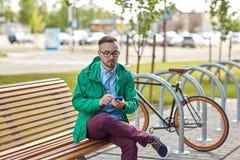 Hombre joven feliz del inconformista con smartphone y la bici Fotos de archivo libres de regalías