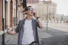 Hombre joven feliz del inconformista que camina en la calle y que habla en el teléfono, con el espacio de la copia Imágenes de archivo libres de regalías