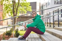 Hombre joven feliz del inconformista que se sienta en las escaleras en ciudad Imágenes de archivo libres de regalías