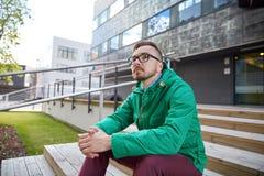 Hombre joven feliz del inconformista que se sienta en las escaleras en ciudad Fotos de archivo libres de regalías