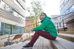 Hombre joven feliz del inconformista que se sienta en las escaleras en ciudad Fotografía de archivo