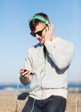 Hombre joven feliz en auriculares con smartphone Imágenes de archivo libres de regalías