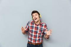 Hombre joven feliz en auriculares que escucha la música y que canta Fotografía de archivo libre de regalías