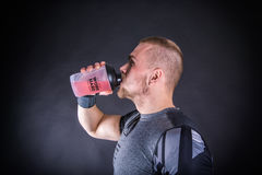 Hombre joven feliz en bebida de consumición de la energía de la ropa de deportes en el gimnasio contra bacground oscuro foto de archivo libre de regalías