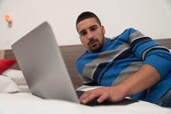 Hombre joven feliz en cama usando el ordenador portátil Imágenes de archivo libres de regalías